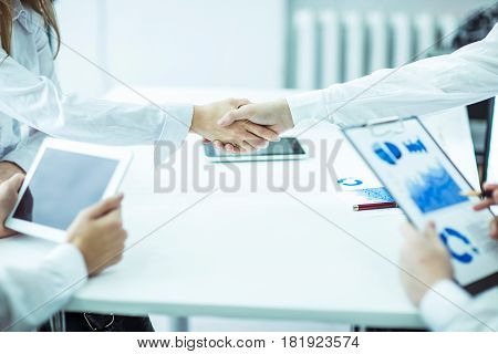 lawyers of the company with financial documents and digital tablet on background of handshake of business partners
