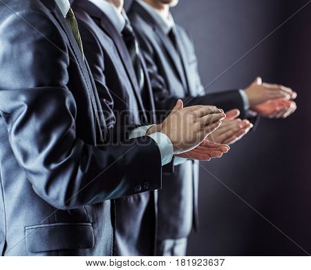 closeup of business team applauding business partners after signing the contract.photo on a black background and has space for your text.