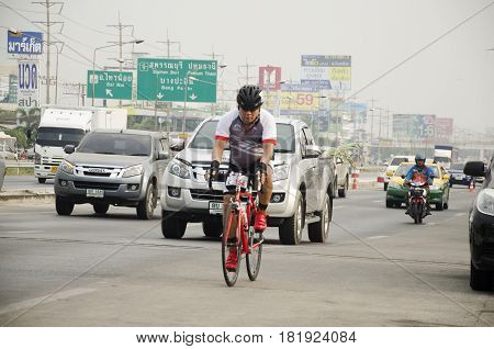 Asian Thai People Biking Bicycle In Race On Street Highway With Traffic Road At Bangbuathong City