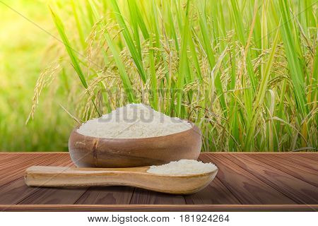 white rice heap in wooden cup and spoon with rice field background