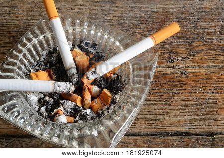 A close up image of a glass ashtray with lit cigarettes and cigarette ashes.