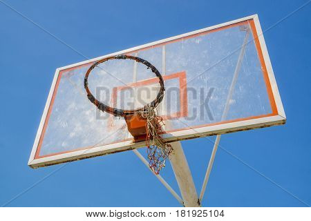 old basketball hoop without net in blue sky background