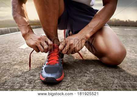 Man tying running shoes and prepare to run