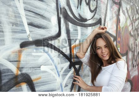 Smiling female portrait next to graffity wall