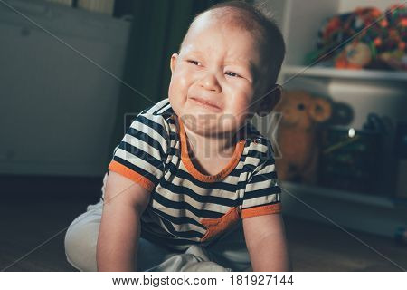 The little boy was crying. The child sits in the room on the floor and roars. Sad and frustrated