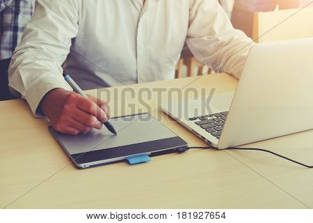 Graphic Designer using digital Drawing tablet and Pen on a computer