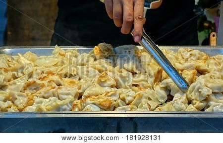 An outdoor vendor sells fried dumplings or pot-stickers