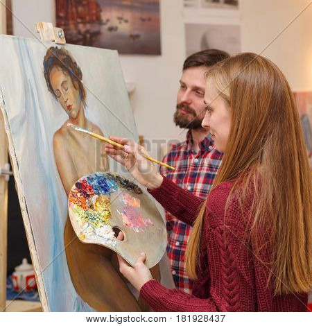 Master class in art school. The girl draws a portrait with oil paints and the teacher comments on the work in the process of execution. Courses of drawing for adults.