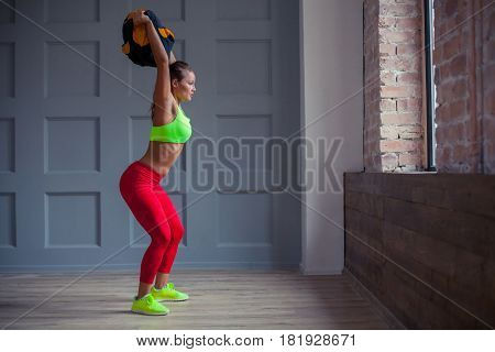 beautiful young woman is training with a sandbag in the gym
