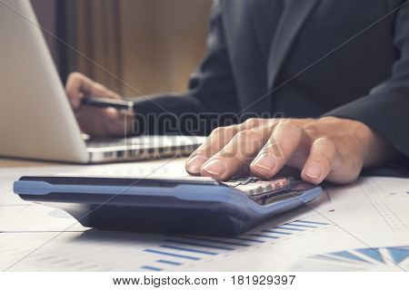 Asian Business man using a calculator to calculate the numbers.Vintage tone