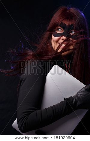 Burglar in mask holds laptop