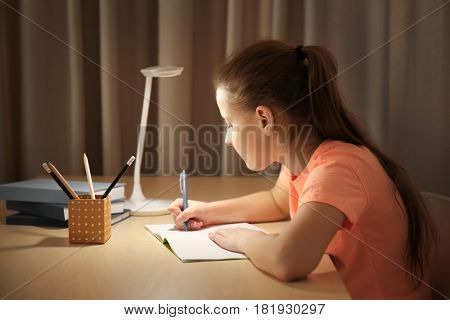 Incorrect posture concept. Schoolgirl sitting at table in room