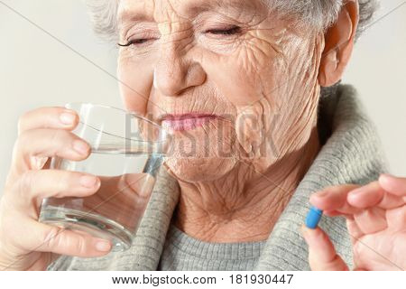 Elderly woman taking pill on light background, closeup