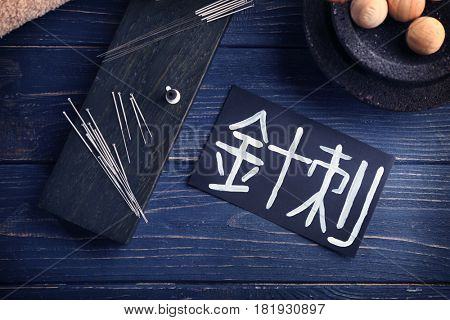 Card with word ACUPUNCTURE in chinese and supplies on table