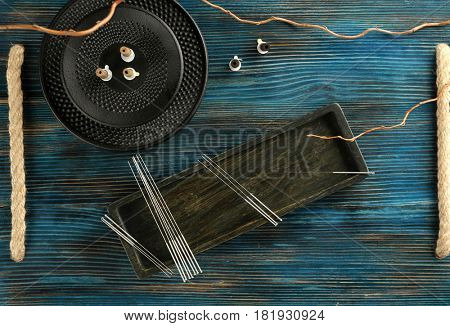 Acupuncture supplies on wooden background