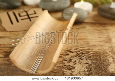 Acupuncture needles on wooden table