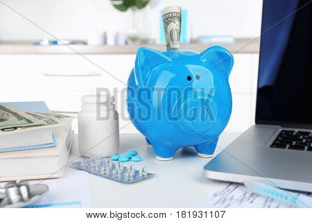 Piggy bank with bottle of pills and banknote on table