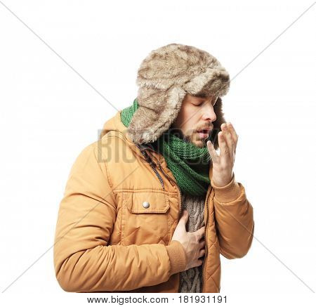Young ill man in warm clothes on white background
