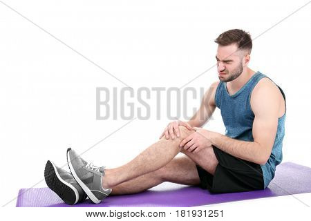 Young sporty man suffering from pain in knee on white background