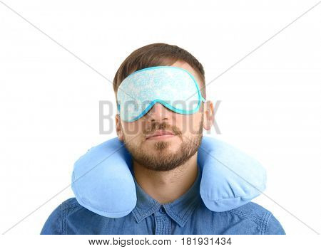 Young man with travel pillow and sleep mask on white background