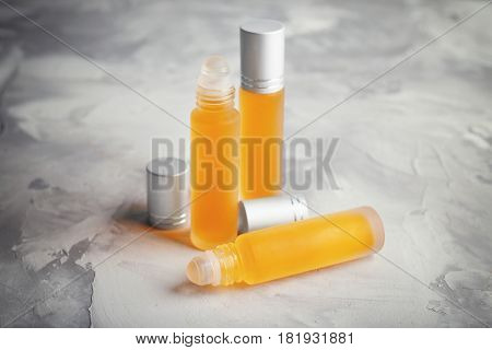 Bottles with perfume on grey textured background