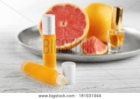 Bottles of perfume and metal tray with citrus fruit on wooden background