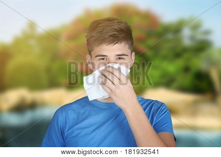 Seasonal allergy. Young man with tissue outdoor