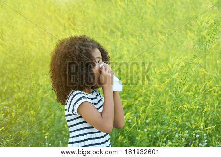 Seasonal allergy. Little African-American girl with tissue outdoor