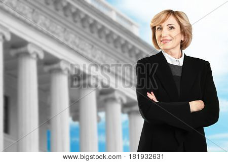 Law and justice concept. Senior woman on courthouse background