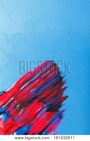 Creativity, modern art, creative abstract painting. Sparkling and shiny smudge nail polish on blue background, with free space for text.