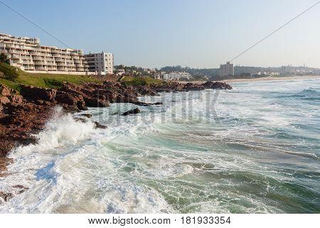 Holiday flat apartments  along beach Rocky Coastline ocean waves landscxape