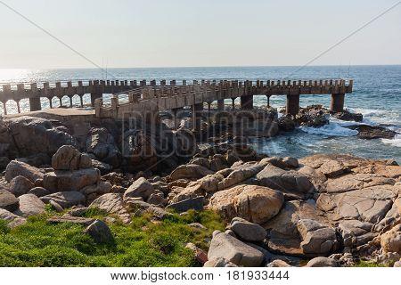 Rocky coastline fishing pier jetty ocean horizon landscape.