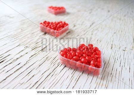 Red cinnamon hearts displayed in heart containers.