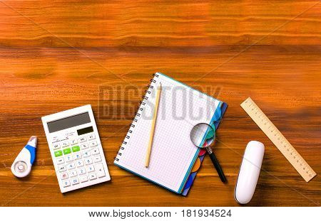 Workspace engineer. Calculator notebook with a spring ruler magnifier pencil stapler on a wooden table