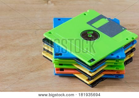 Multicolor diskette stacked on brown wood background