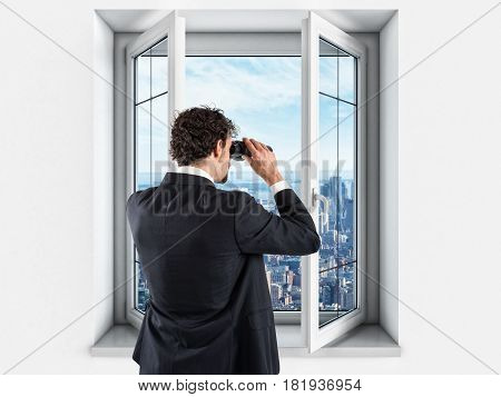 Businessman looks at the city from the window of build with binoculars