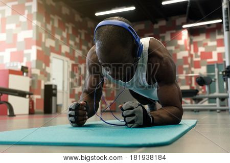 Confident muscled young black man wearing sport wear and doing plank position while exercising on the floor in gym