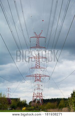 Pylon of high voltage transmission line. Cloudy sky in background.