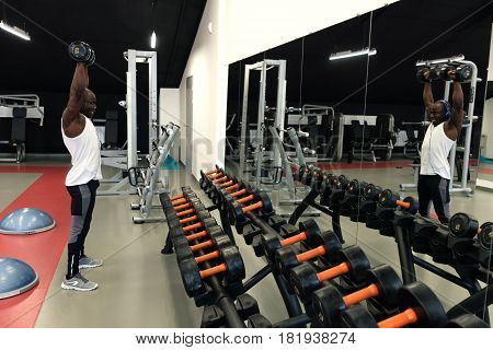 Muscular black man in a white t-shirt doing exercises with dumbbells in front of the mirror at gym
