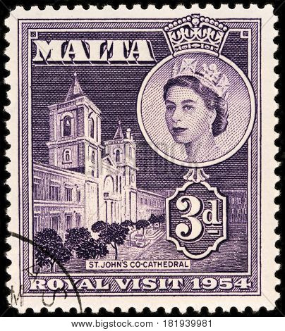 LUGA RUSSIA - FEBRUARY 7 2017: A stamp printed by MALTA shows image portrait Queen Elizabeth II against view of Roman Catholic Saint John's Co-Cathedral in Valletta Malta circa 1954.
