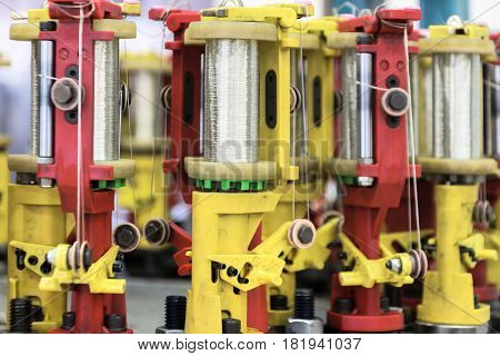 Modern braiding machine. Machine mechanism, holders for bobbins with wire. Selective focus.