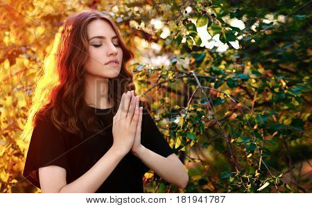 The girl prays in nature. eyes closed