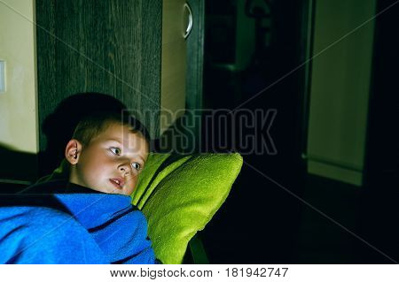 a frightened little boy in bed .Night terrors