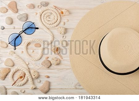 Sun glasses and hat on a light wooden background. Selective focus.