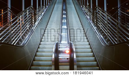 Low angle and close up view at a long escalator in public building. night scene .