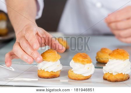 Pastry chef finishing a delicious cream profiteroles