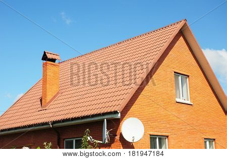 Red old metal house roof tiles. Metal Roof Shingles - Roofing Construction Chimney Attic Exterior Roofing Repair.