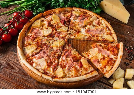 Appetizing fresh pizza with ham, cheese and pineapple, served on rustic wooden table with ingredients, top view. Cut bite off slice.