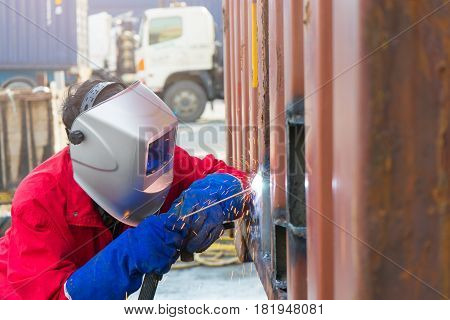 Welder worker repair the damage container wall Industrial at the factory welding. Worker repair container box by gas cutting and welding heavy job. worker while doing a welding with arc welder