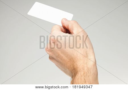 Male Hand Holds White Card Over Gray